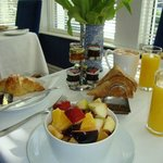 Freshly made fruit salad with toast, croissants and coffee