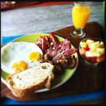 Breakfast - fried eggs, bacon, mushroom and tomato served with juice, fruit salad and a cappucci