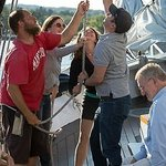 Crew and passengers raising the foresail.