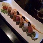 Rainbow Roll sushi - California roll with Sashimi.  Includes red pepper sauce and teriyaki glaze