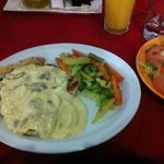 Chicken with a white sauce with mushrooms, vegetables with garlic and a salad