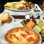 Corned beef hash eggs benedict and lobster quiche with fruit.