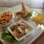 Calamari alla cardinale su letto di polenta, insalata di mare tiepida e gamber