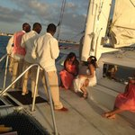 The bride, sister & groomsmen enjoying the catamaran deck at sunset