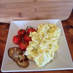 Hand whipped scrambled eggs. Old world style. With roasted tomato, mushrooms. Over Rustic bread.
