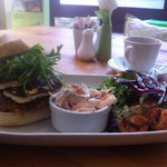 Vege burger topped with grilled halloumi in a ciabatta bun with balsamic drizzled salad and home