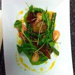 Dive caught pan fried scallops with pea purée, pea shoots, Parma ham shards prawns and saffron o