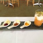 Glass of cherry tomato coulis, sour cream spoons with jam and cheese