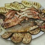 Grigliata di pesce sul letto di verdure grigliate