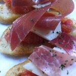 Crostini with tomato, prosciutto and local cheese