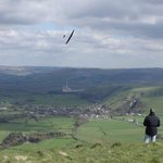 Guy flying his glider near the top of Mam Tor, with Castleton beneath