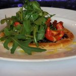 Red Onion and Tomato Tart with wild rocket and lime creme fraiche.