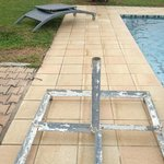 Broken deck chair & umbrella stand by the pool