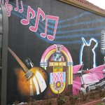 A rock and roll mural on the side of the hotel.