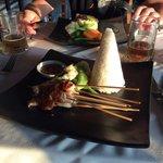 satay sticks at front, fish and risotto at back