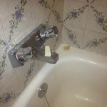 Broken shower lever and dirty bathtub and grout.