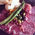Butcher block, assorted meats, cheeses, olives.