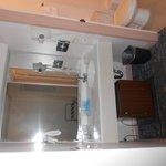 Vanity sink, mirror and small fridge underneath