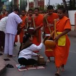 people giving food to Buddhist monks at sunrise