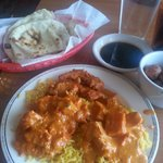 At the top is naan(bread served w/meal). On the plate is chicken tikka masala, sweet potato masa