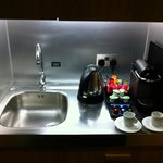 Small kitchenette area with fridge, kettle, sink, microwave and nespresso machine and capsules