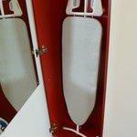 En otra puerta del armario hay una tabla de planchar y una plancha