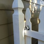 tiny birdhouse on the pristine white picket fence near our door
