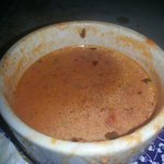 Tomato basil bisque creamy with small bits of chopped tomatoes and translucent onions
