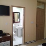 Poorly furnished room, glass pane above entrance offers no privacy