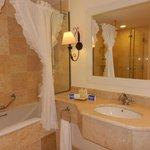 Baño de la habitación con tina y ducha a parte. El sanitario está separado con una puerta .