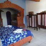 Habitación co cama, roperos, jacuzzi, baño y chimenea.