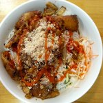 Fried egg rolls and grilled pork over vermicelli noodles, fresh veggies and herbs