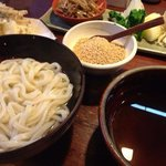 The udon is served with a bowl of sesame seeds and seasonal vegetables