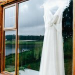 View of the dress hanging in the window of the double-storey log cabin