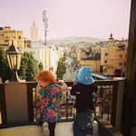 The children looking over the city from the rooftop patio