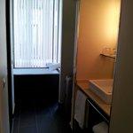 справа раковина, слева двери в душ и туалет