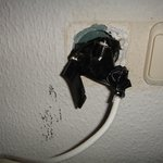 Hazardous TV wall-outlet with lot of exposed cables