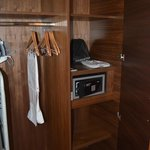 Wardrobe space with a safe, hangers, iron, ironing board, hair-dryer, slippers, robes and more.