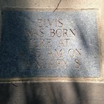 A stone describing Elvis Presley's time of birth (a nearby stone says he was born in 1935)