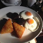 Breakfast of hash browns, black pudding, and poached eggs.