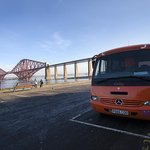 Dolly, the Hairy Coo Bus, parked at the Forth Bridge.