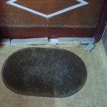 Dirty doormat and broken stones in front of bathroom