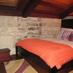 A los pies de la cama hay un banquito junto a la pared para subirte y ver el exterior por la ven