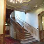 Main staircase in the hall, oposite of the well equipped bar