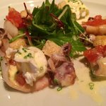 Warm squid salad with confited tomatoes, salad, beurre blanc and perfectly poached quail eggs -
