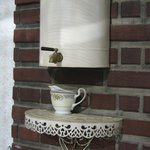 Love this water cooler attached to the brick wall on the front screened porch.