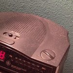 Finger through dust on alarm clock by edge of dots see!