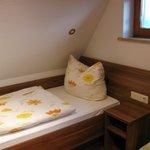 A cama de solteiro sob o teto inclinado.