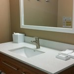 Sink with ample space for toiletries, towels, drawer, and shelving.