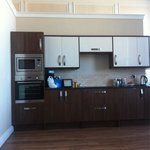 One view of the kitchen. Around  the corner is your sink and fridge. In front is your modern tab